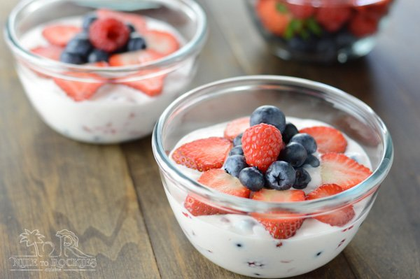 A bowl of fruit on a plate, with Cream and Fruit salad