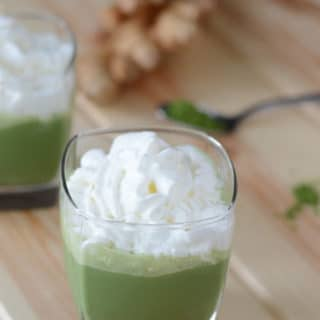 A close up of a glass cup on a table, with Matcha smoothie