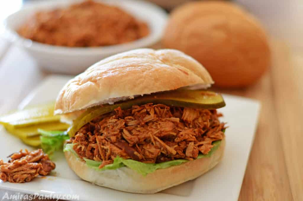 a pulled bbq chicken sandwich on a white plate with a bowl of pulled chicken in the back