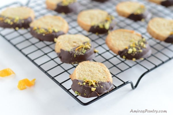 Easy orange cookies, dipped in dark chocolate and sprinkled with orange zest and pistachios. Perfect for tea time or coffee time..