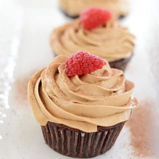 A close up of a Coffee Cupcake with Raspberry on top