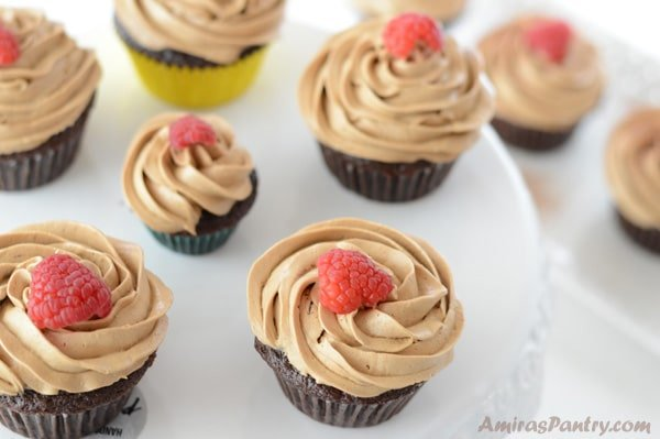 Moist and fluffy, rich in coffee flavor cupcakes filled with a luscious raspberry preserve and topped with a delicious coffee buttercream frosting. A coffee cupcake recipe from scratch that is a coffee addict dream.