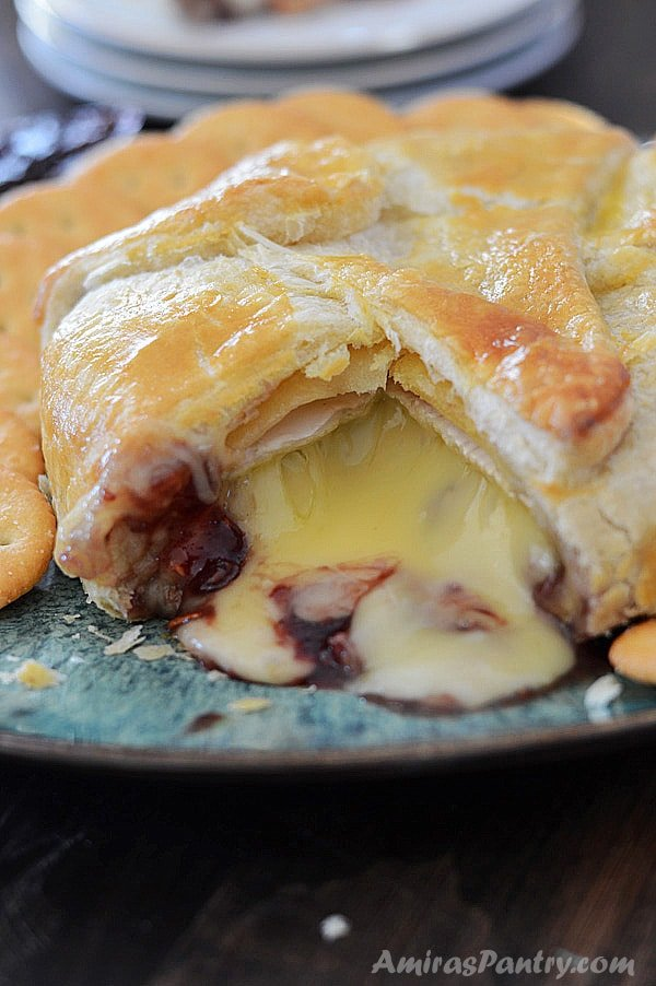 Baked brie in puff pastry on a plate with cheese and raspberry jam oozing out of it