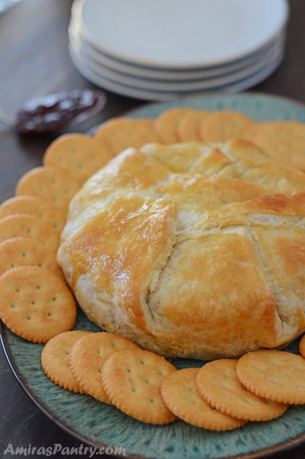 Bake brie puff pastry on a serving plate with crackers around