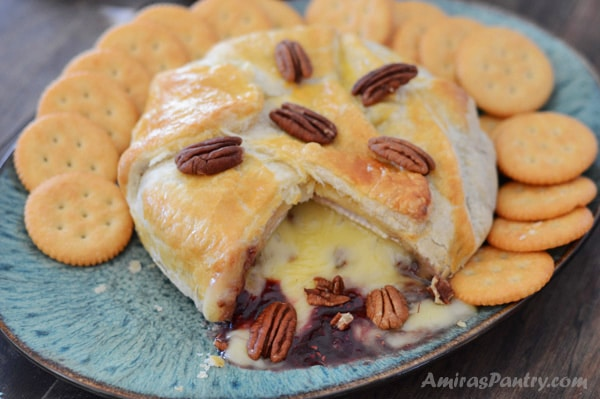 baked brie puff pastry on a serving plate with crackers all around and cheese is melted and ozzing out of the puff pastry