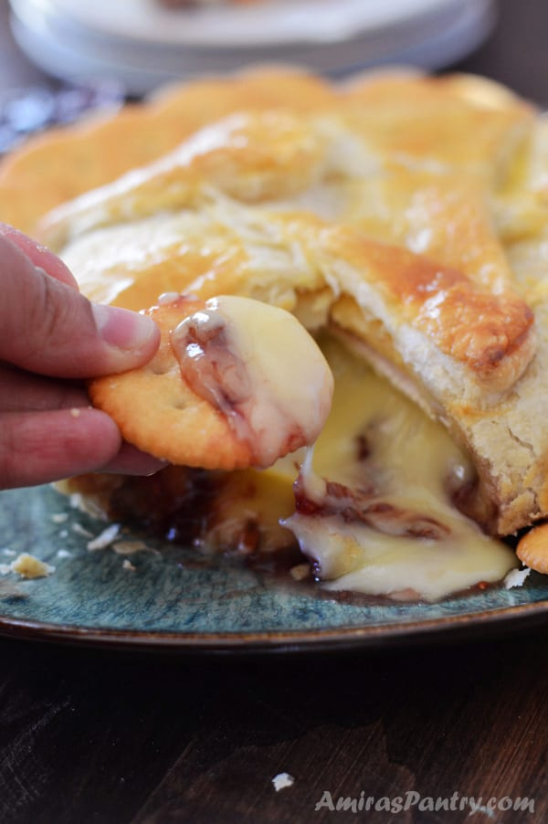 A hand dipping crackers in baked brie puff pastry with cheese dripping from the cracker