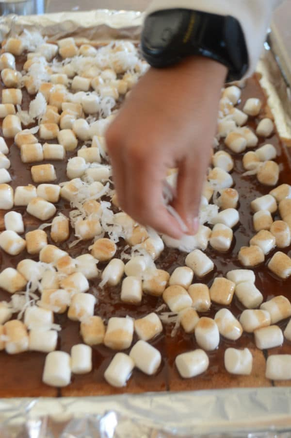 A photo showing a pan with biscuits, Marshmallow and a hand