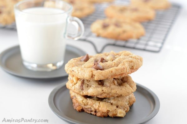 A close up of a plate of oatmeal cookies and cup of milk