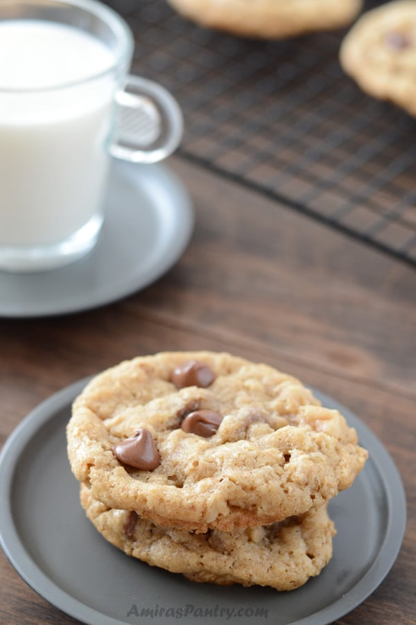 A close up of a plate of food and a cup of milk, with Oatmeal cookie