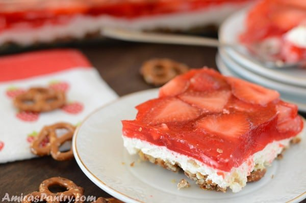 A piece of strawberry pretzel salad on a plate with some pretzels scattered on the table.