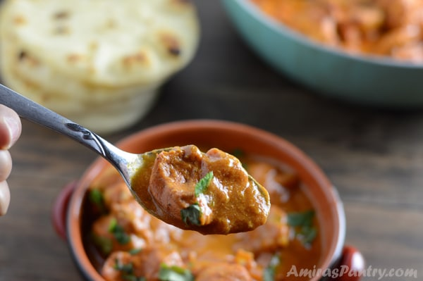 A bowl of food on a table with Chicken tikka and spoon