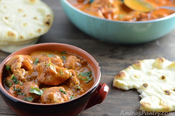 A bowl of food on a table with Chicken tikka and bread