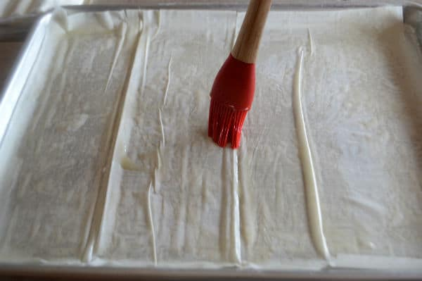 A photo showing sheets of pastry and brush