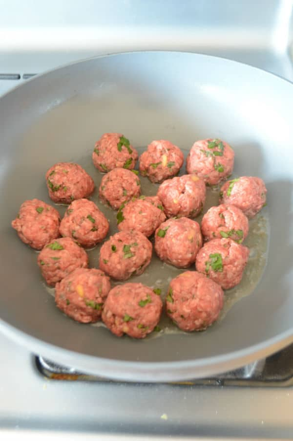 A bowl of food on a stove, with meatballs
