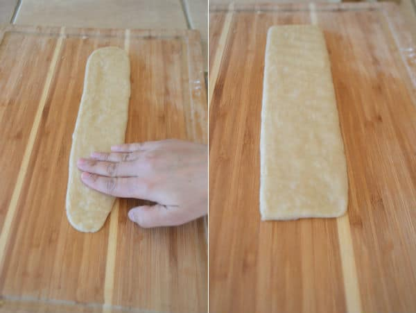 A wooden cutting board, with pieces of dough and hand
