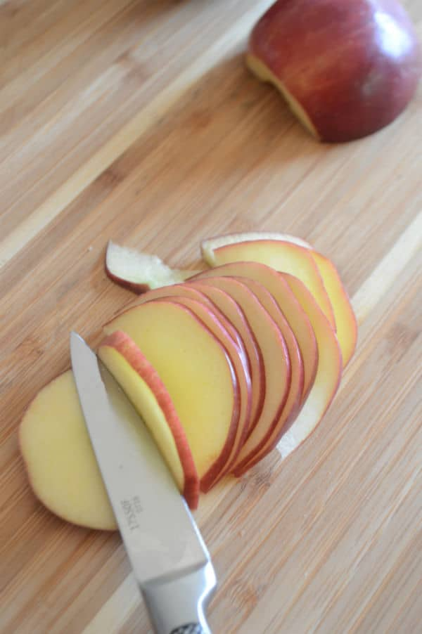 An apple sitting on top of a wooden cutting board, cut into slices