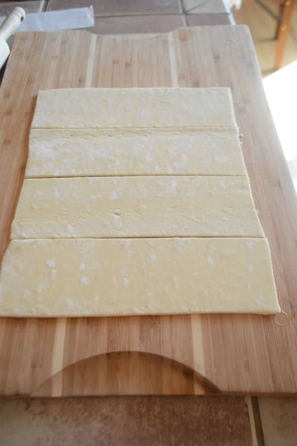 A wooden cutting board, with dough strips