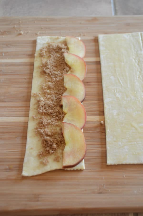 A piece of dough with mixture, apple slices on a wooden cutting board