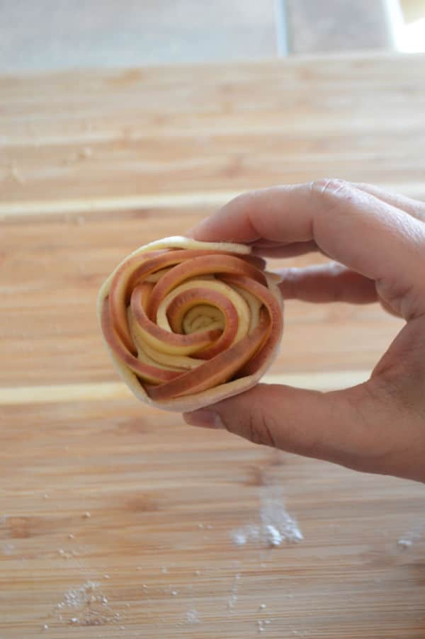 A hand holding rolled dough with apple slices inside