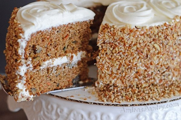 A slice of the carrot cake being cut from the whole cake.