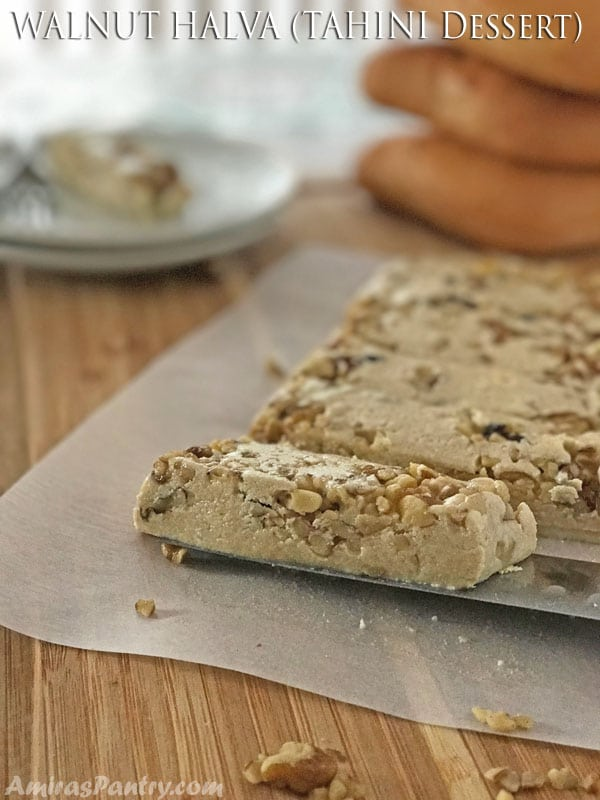 A slice of Halva sitting on top of a wooden cutting board, with nuts