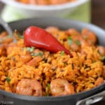 A dish is filled in food, with yellow Rice and spicy shrimp