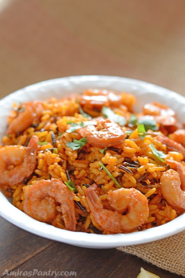 A plate of spicy wild rice and shrimp ganrished with fresh cilantro