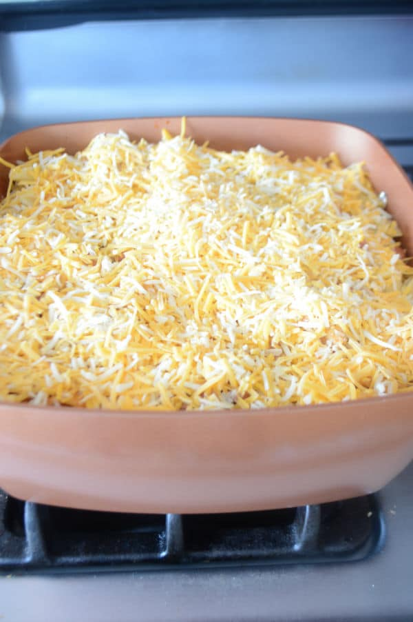 A pan of food on a stove with pasta and cheese