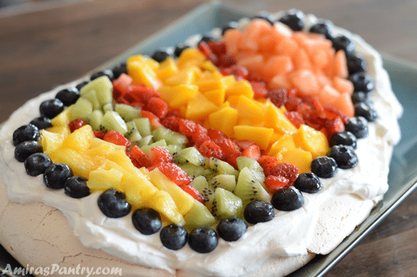 A plate of food on a table, with Pavlova and Fruit