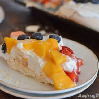 A piece of cake on a plate with fruits