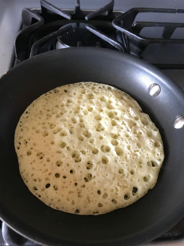 Step 3 of making Moroccan baghrir, cooking the pancakes in a skillet.