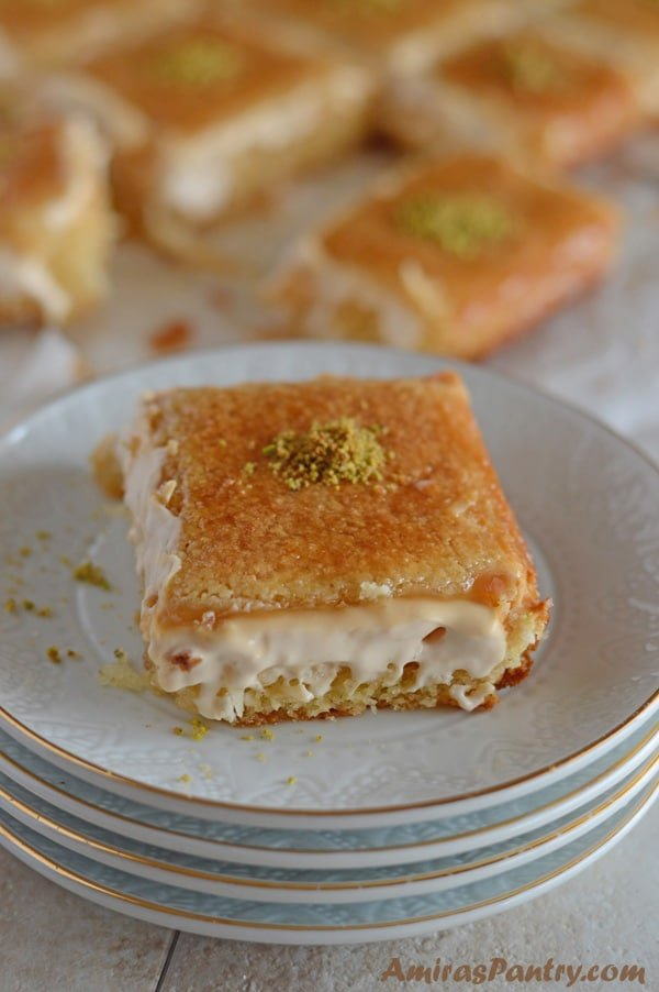 A piece of cake on a plate with Basbousa and cream