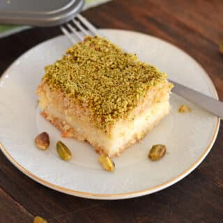 a maamoul piece on a white plate garnished with crushed pistachios.