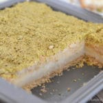 A piece of cake in a pan with maamoul mad pistachios