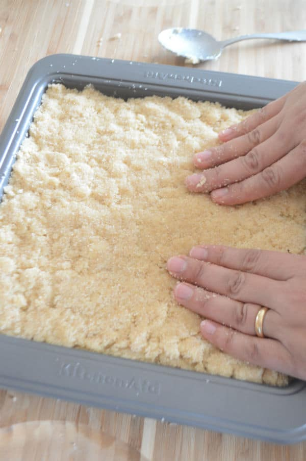 A hand mixing dough in a pan
