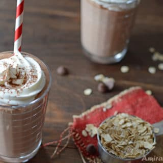 A cup of Nutella protein shake on a table with straw
