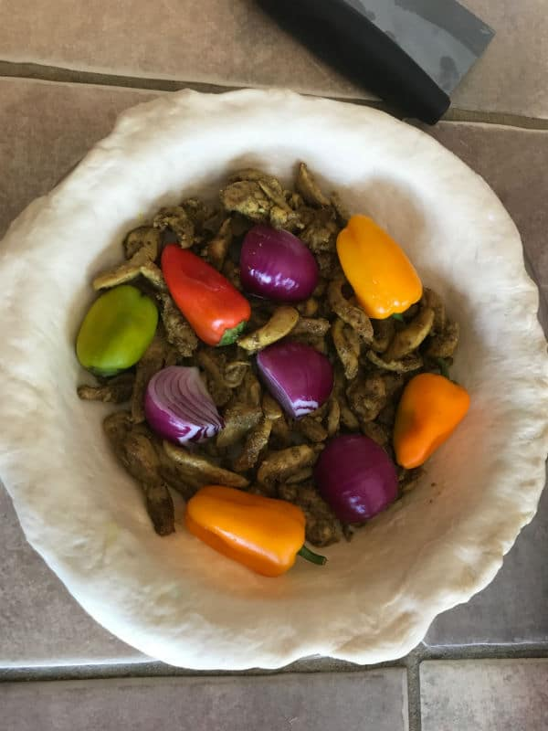 A bowl of food, with Shawarma and vegetables before baking