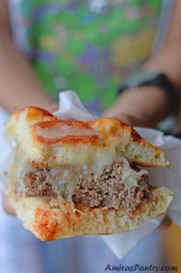 Little Hands holding a quarter of the pizza burger ready to be eaten.