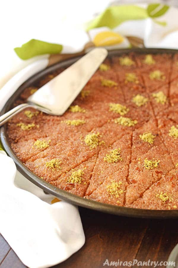 Basbousa pan, cut into diamond shapes and garnished with crushed pistachios. With a serving spatual on top.