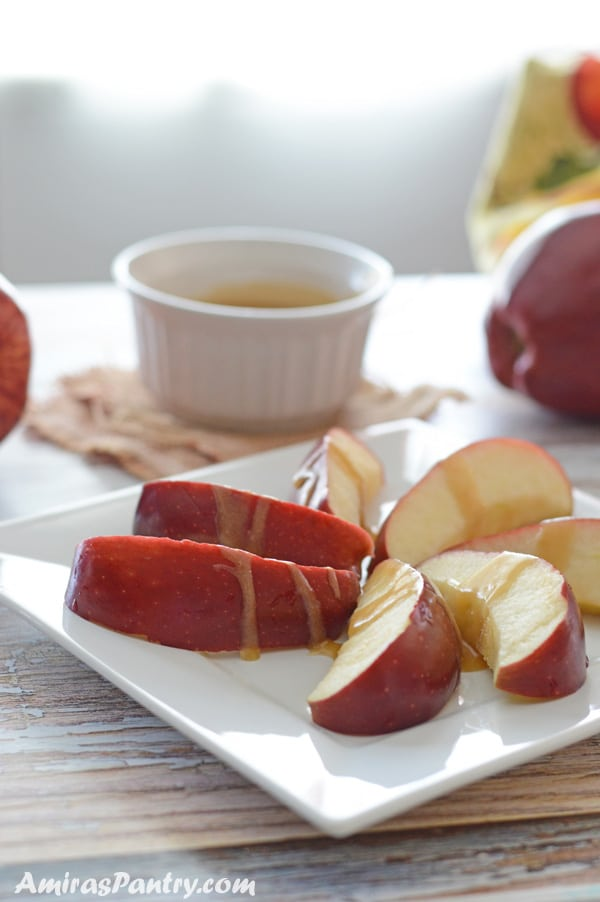 Apple slices on a white plate drizzled with date sauce