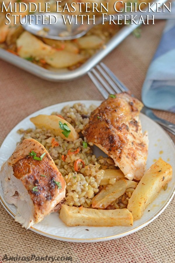 A plate with a chicken breast cut in half with some freekeh and roasted potatoes.