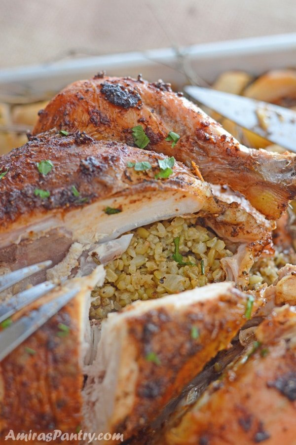 A chicken cut open to show freekeh inside and a fork on the side.