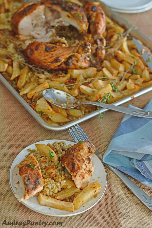Chicken breast cut in half on a plate with some freekeh and potatoes and the whole baking dish with the rest of the chicken in the back.