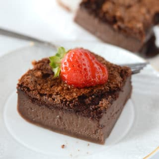A piece of chocolate cake on a plate with strawberry