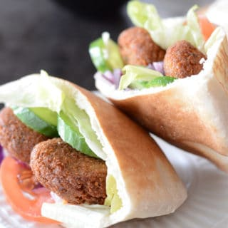 A close up of a pita bread cut on a plate, with Falafel and vegetables