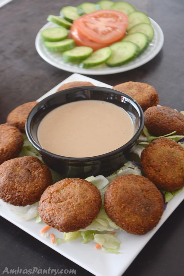 A plate of food on a table, with Falafel and dip