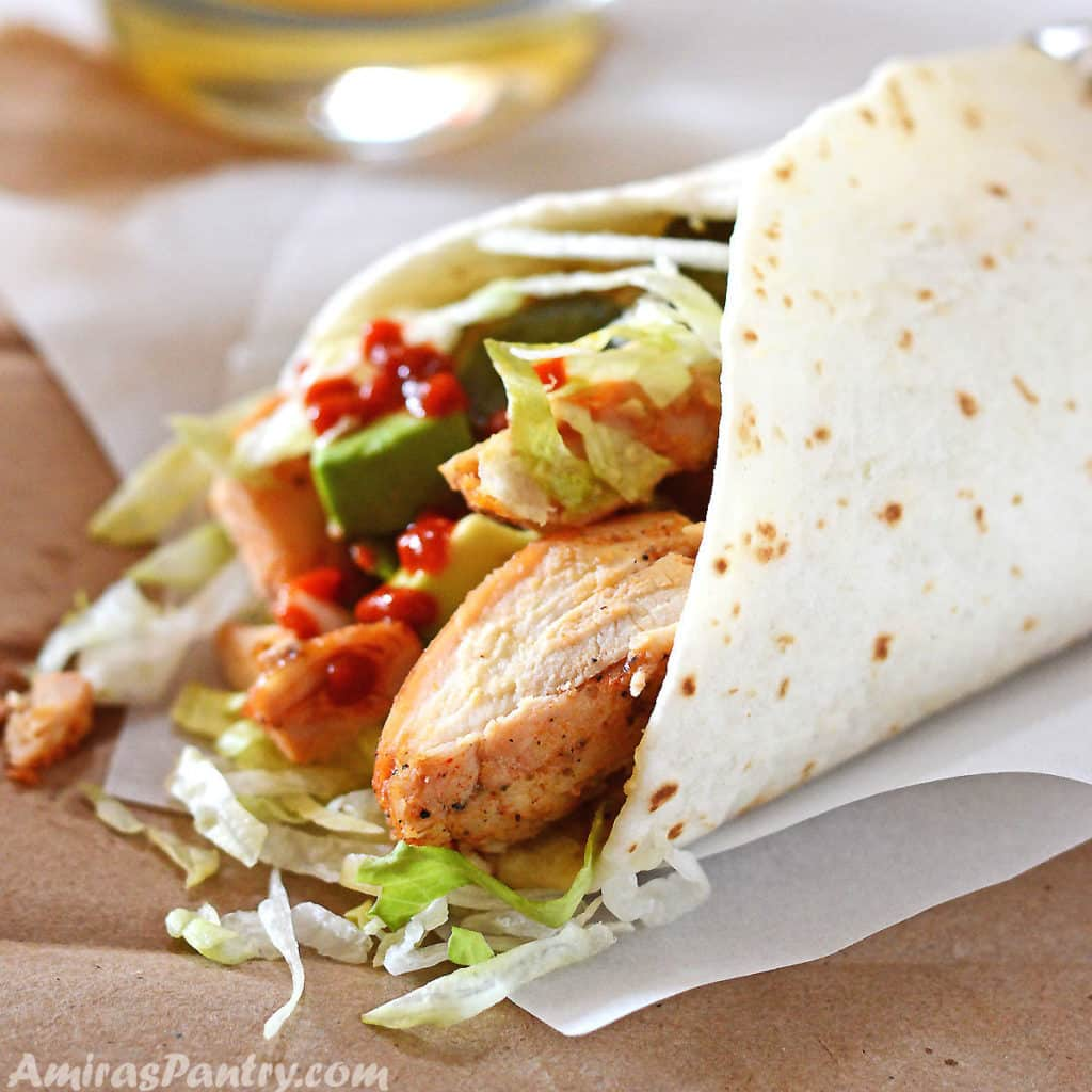 Baked Chicken Thighs wrapped in a tortilla bread with lettuce on a white parchment paper.