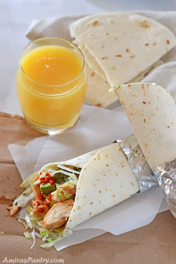Baked chicken thigh wraps on parchment paper with a cup of orange juice.