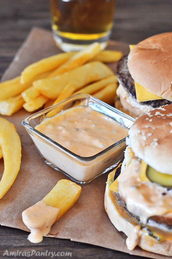 Two homemade big mac sandwiches with fries on the side and a small bowl filled with big mac sauce.
