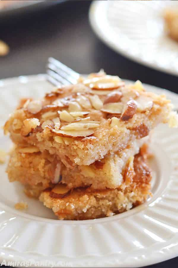 A stack of basbousa squares on a white plate topped with almonds.